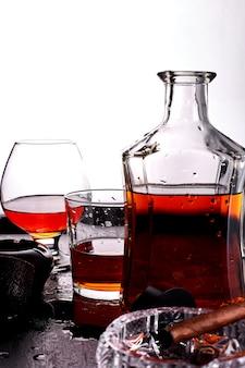 Glas whisky mit rauchender zigarre.