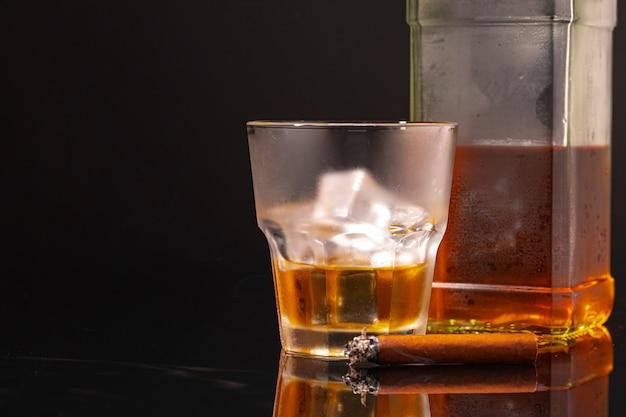 Glas whisky und brennende zigarre auf schwarzem hintergrund schließen