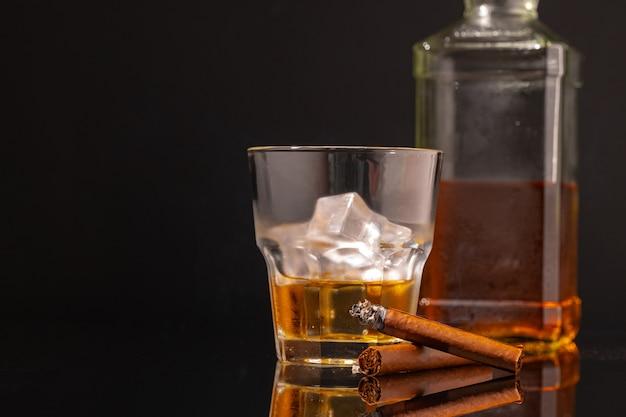 Glas whisky und brennende zigarre auf schwarzem hintergrund