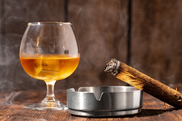 Glas whisky und brennende zigarre in einem aschenbecher