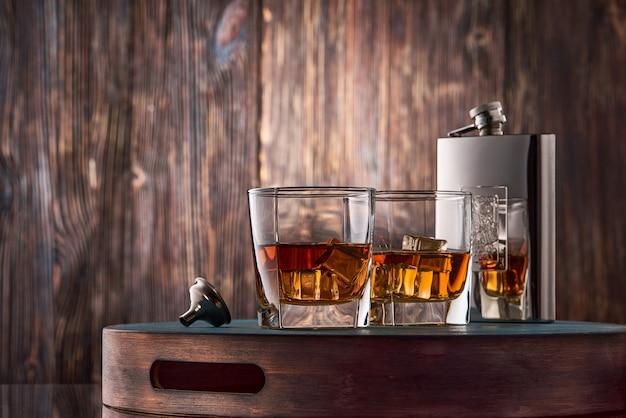Glas whisky und eine flasche auf dem holztisch