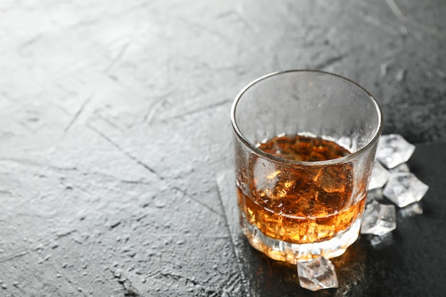 Glas whisky und eiswürfel auf schwarzem hintergrund, kopienraum