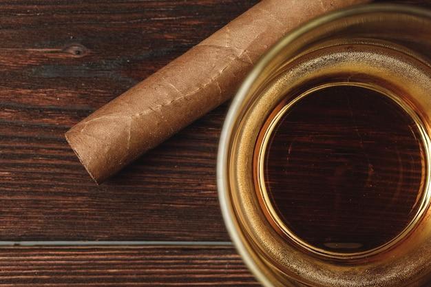 Glas whisky und gerollte zigarren auf holztisch