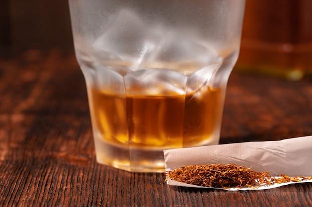 Glas whisky und zigarettenpapier mit tabak