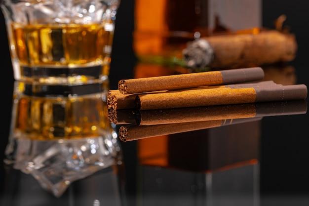 Glas whisky und zigarre auf schwarzem tisch