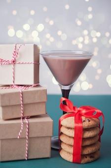 Glas wintersaisonschokoladencocktail, weihnachtsgeschenkboxen, plätzchen auf der grünen tabelle