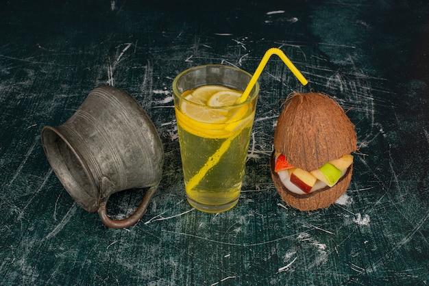 Glas zitronenwasser mit kokosnuss und alter tasse