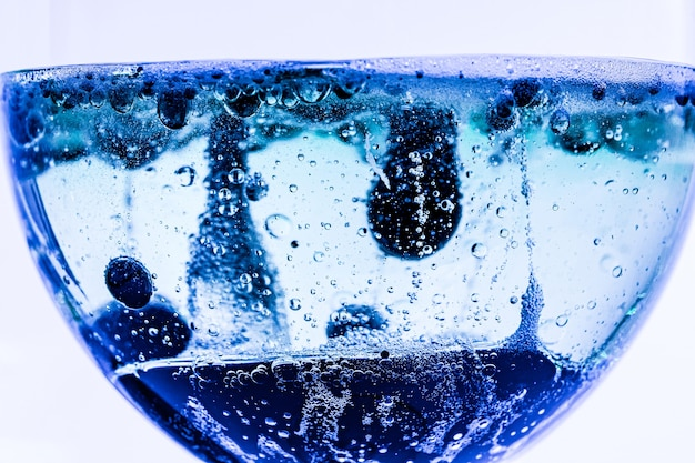 Glasbecher mit blauer flüssigkeit und blasen