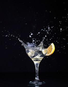 Glasbecher mit gin tonic cocktail mit spritzern und zitrone auf isoliertem schwarz