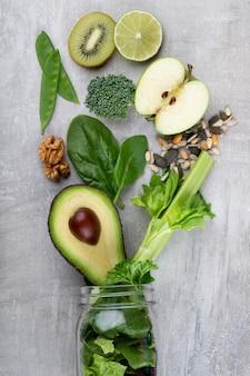 Glasbecher mit grünem gesundheitsgemüse salatblätter, limette, apfel, kiwi, avocado, lebensmittelkonzept.