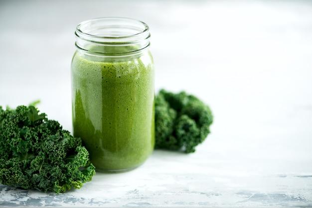 Glasbecher mit grünem gesundheitssmoothie, kohlblättern, kalk, apfel, kiwi, trauben, banane, avocado, kopfsalat.