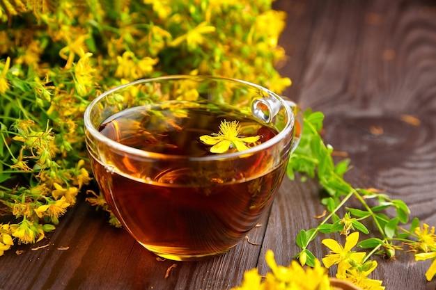 Glasbecher mit hypericum perforatum pflanzengetränk mit kräutermedizin mit frischen blumen