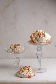 Glasbecher mit sahneeis, karamellsauce und nüssen.