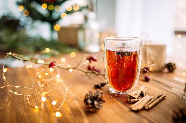 Glasbecher schwarzer tee mit sternanis auf dem hölzernen festlichen tisch mit girlandenlichtern