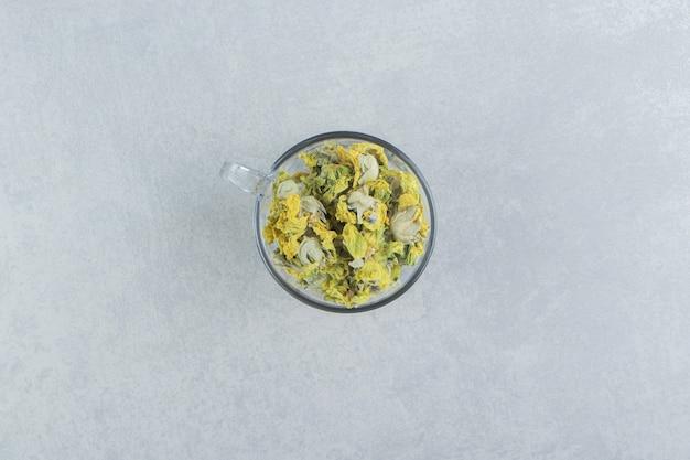 Glasbecher voller gelber blumen