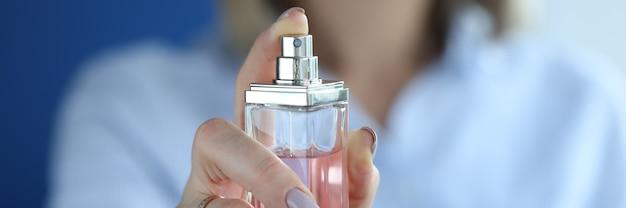 Glasbehälter mit parfüm ist in frauenhänden. damenparfüm und sein typenkonzept