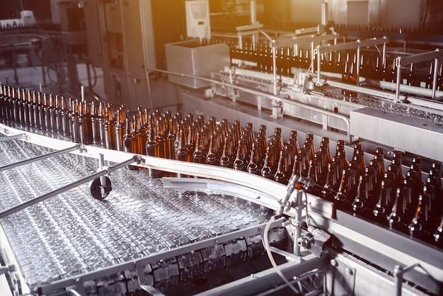 Glasbierflaschen von brauner farbe auf der förderstrecke
