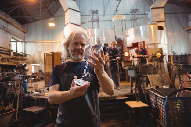 Glasbläser, der glaswaren untersucht, während kollegen arbeiten