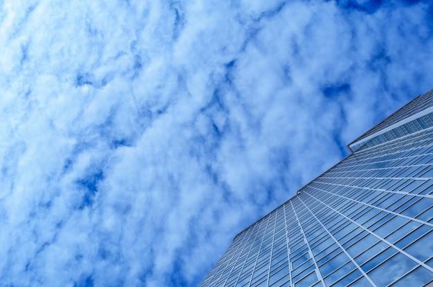 Glasbürogebäudewolkenkratzer auf einem hintergrund von wolken