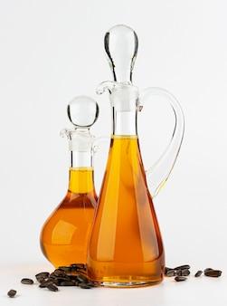 Glasdekanter mit sonnenblumenöl lokalisiert auf weißem tisch
