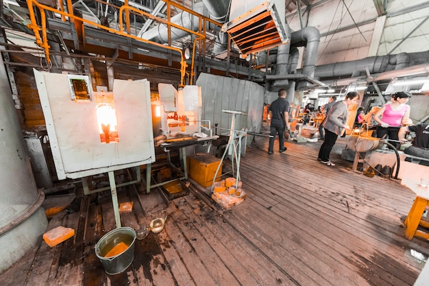 Glasfabrikarbeiter auf der produktion des glases arbeitend mit herstellungsausrüstung