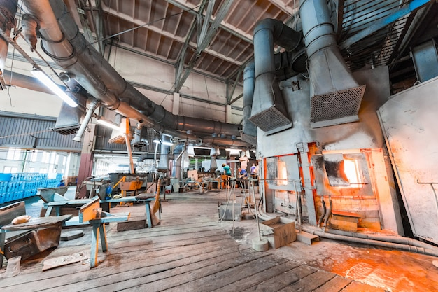 Glasfabrikarbeiter auf produktion des glases mit herstellungsausrüstung