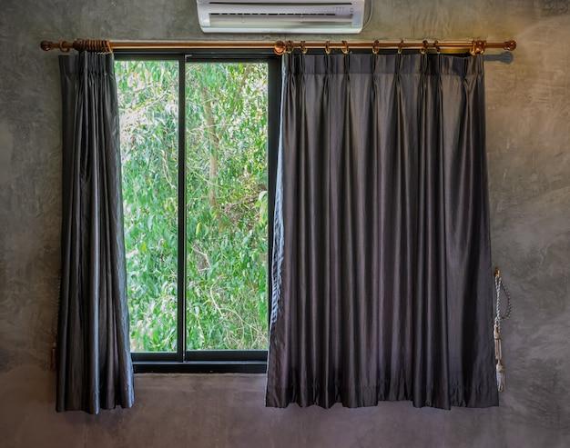 Glasfenster mit offenem vorhang und grünem garten auf hintergrund