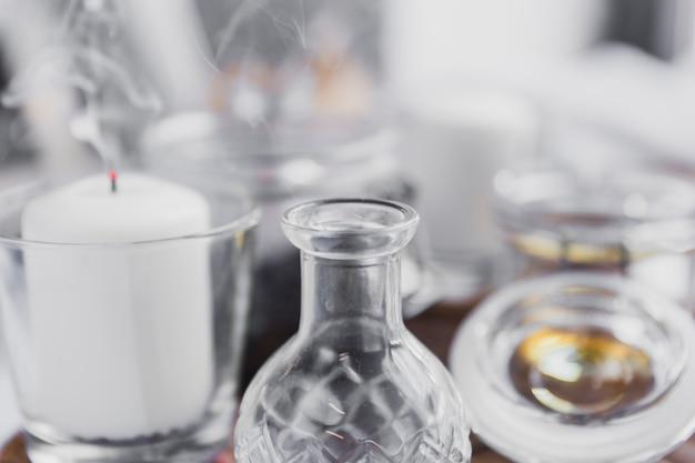 Glasfläschchen in der nähe von kerzen