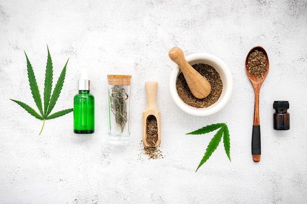 Glasflasche cannabisöl mit weißem mörser und hanfblättern auf beton.