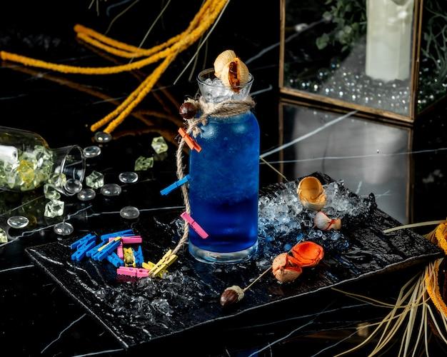Glasflasche der blauen lagune verziert mit seil und bunter wäscheklammer