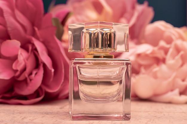 Glasflasche des duftenden eau de toilette vor dem hintergrund der rosa pfingstrosen. weibliches parfümkonzept. attrappe, lehrmodell, simulation. nahaufnahmefoto