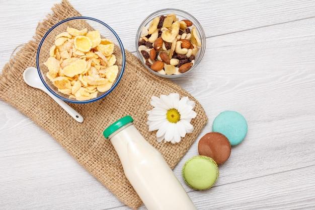 Glasflasche frische milch, schüsseln mit müsli und cornflakes, kamillenblüten und makronen auf sackleinen. ansicht von oben