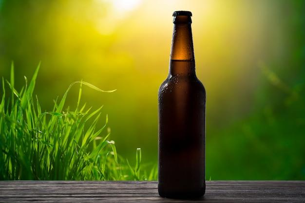 Glasflasche kaltes bier auf einem hintergrund eines sommergartens