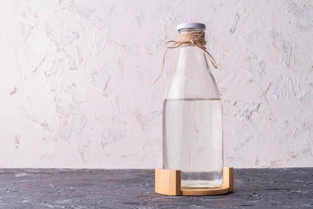 Glasflasche mit absolut sauberem destilliertem wasser lokalisiert auf schmutzoberflächen
