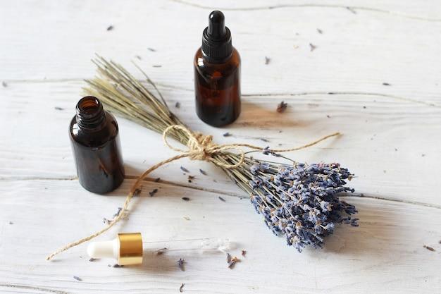 Glasflasche mit bio-kosmetik mit einem bündel lavendel. blogging beauty-konzept