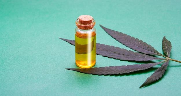 Glasflasche mit cannabisöl in der nähe der pflanze