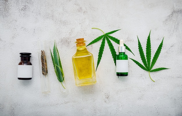 Glasflasche mit cannabisöl und hanfblättern auf beton.