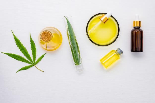 Glasflasche mit cannabisöl und hanfblättern auf weiß.