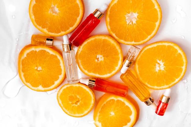 Glasflasche mit flüssigem kollagen und hyaluronsäure mit orangenscheiben