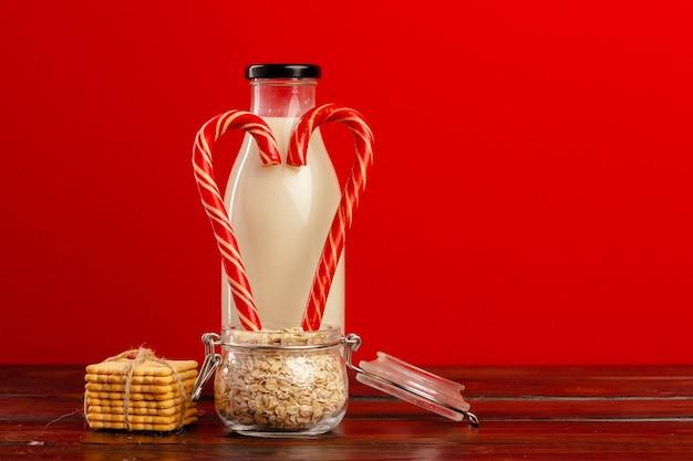 Glasflasche mit frischer milch und zuckerstangen auf holztisch