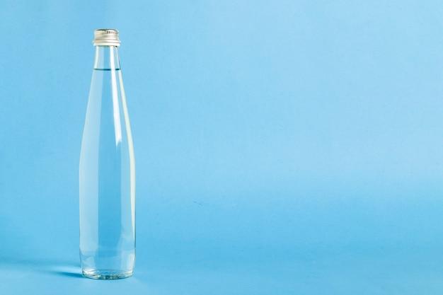 Glasflasche mit haarscharfem auffrischungswasser auf einer blauen oberfläche. konzept von schönheit und gesundheit, wasserhaushalt, durst, sommer