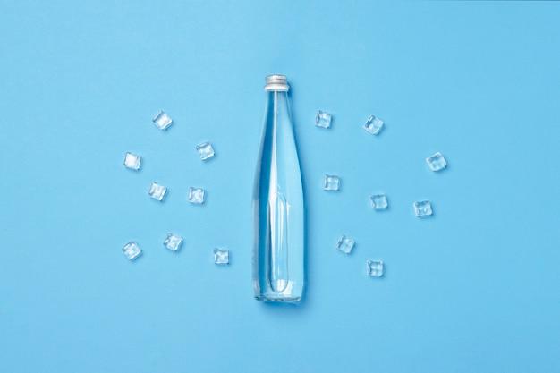 Glasflasche mit klarem wasser auf einer blauen oberfläche mit eiswürfeln. konzept von gesundheit und schönheit, wasserhaushalt, durst, hitze, sommer. flachgelegt, draufsicht.