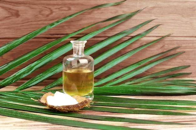 Glasflasche mit öl, sahne in kokosrinde und palmblatt auf holzoberfläche