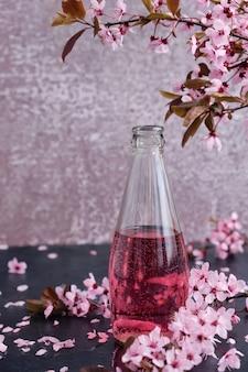 Glasflasche mit rosa getränk, mit blütenkirschzweigen oben