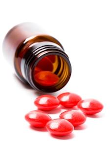 Glasflasche mit roten pillen auf weißem hintergrund