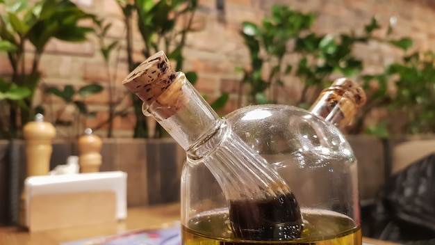 Glasflasche mit sauce und butter für pizza und pasta, stehend auf einem servierten holztisch in einem italienischen restaurant mit ziegelwänden und grünpflanzen.