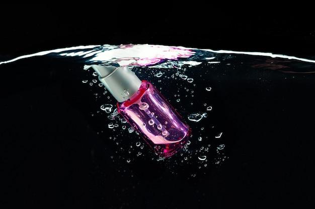 Glasflasche mit spender, der in wasser gegen dunklen hintergrund nah oben taucht