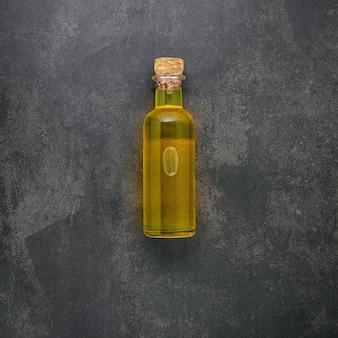 Glasflasche olivenöl auf dunklem betonhintergrund.