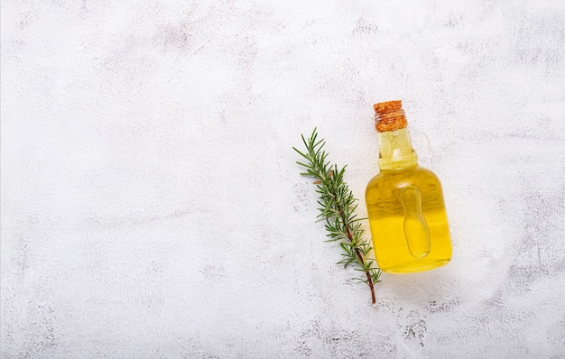 Glasflasche olivenöl auf weißem betonhintergrund.