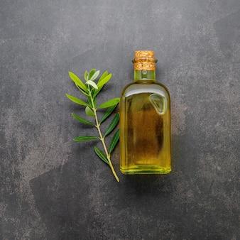 Glasflasche olivenöl und olivenzweig auf dunklem betonhintergrund.